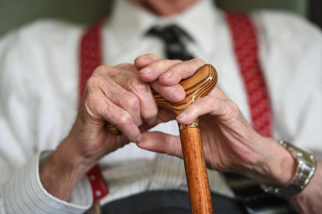 Hands of an older person holding a walking stick
