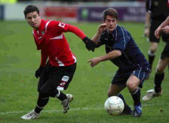 Danny Cox, left, takes on the Poppies defence