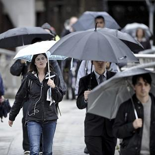 Commuters with umbrellas make their way across Millennium Bridge in Bristol, where there has been a weather warning