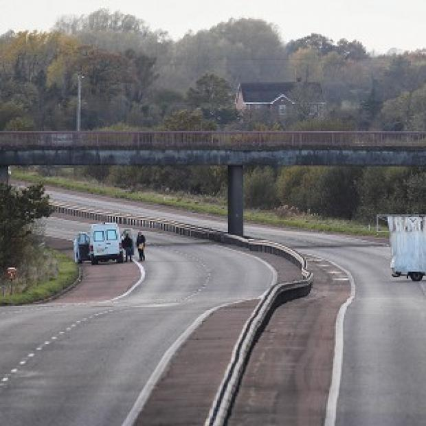 Police at the scene on Northern Ireland's M1 motorway where Prison Officer David Black was shot dead