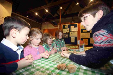 Children learn to bake bread at the mill.