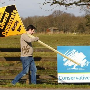 A Liberal Democrat supporter passes a Conservative banner as he prepares to erect a party advertisement in Eastleigh, Hampshire