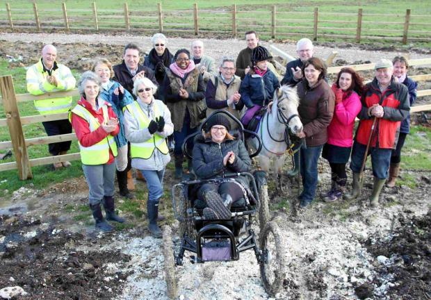 Romsey Advertiser: Emma Weavil in a BOMA electric powered off-road wheelchair with staff and guests on the remodelled chalk mounds celebrating the start of the project