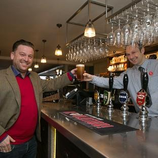 Romsey Advertiser: Tom from Beaconsfield, left, buys the first pint from shift manager Derek at the new JD Wetherspoon pub called Hope And Champion at the M40 services at Beaconsfield