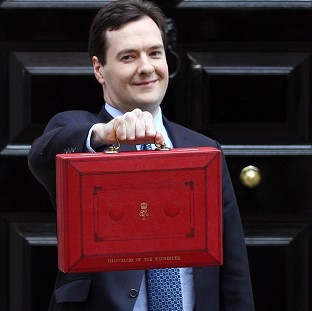 Chancellor George Osborne holds up his red Ministerial Box outside 11 Downing Street before heading to the Commons to deliver his annual Budget statement