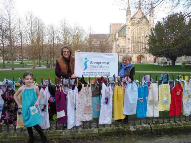 Romsey Advertiser: Seven year old Caitlin Scott modelling one of the pillowcase dresses, SI Winchester members Carol Forse and Gina Bird.
