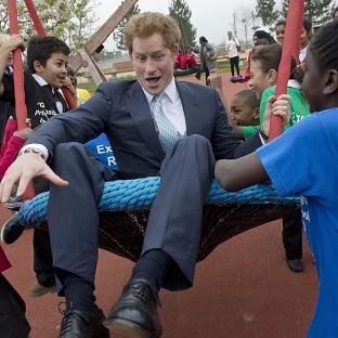 Romsey Advertiser: Prince Harry on a swing with local school children from Gainsborough Primary school in Newham