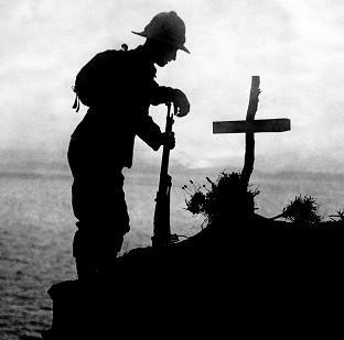 A soldier pays his respects at the grave of a colleague near Cape Helles, where