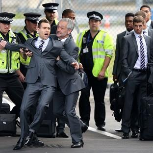 Romsey Advertiser: Comedian Simon Brodkin is taken away from the England team by security at Luton Airport