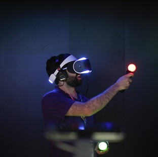Jordan Saleh plays a video game with Sony's Project Morpheus virtual reality headset at the Electronic Entertainment Expo in Los Angeles. (AP Photo/Jae C. Hong)