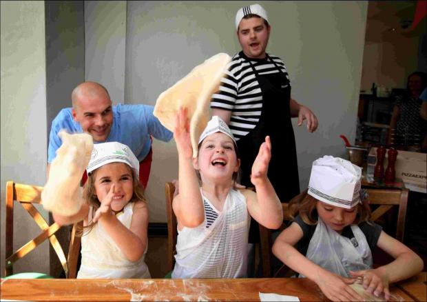 Staff members Fabio Kersevan and Matt Bristown helped the children learn the best techniques for tossing the dough