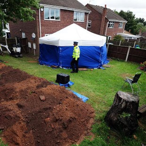 Romsey Advertiser: Police in the garden of a house in Mansfield, where the remains of William and Patricia Wycherley were discovered