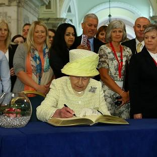 Romsey Advertiser: The Queen signs a book following her visit to the Belfast City Hall