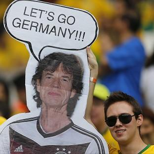 Brazil fans hold a poster depicting Rolling Stones singer Sir Mick Jagger wearing a Germany shirt before the World Cup semifinal match between Brazil and Germany (AP)
