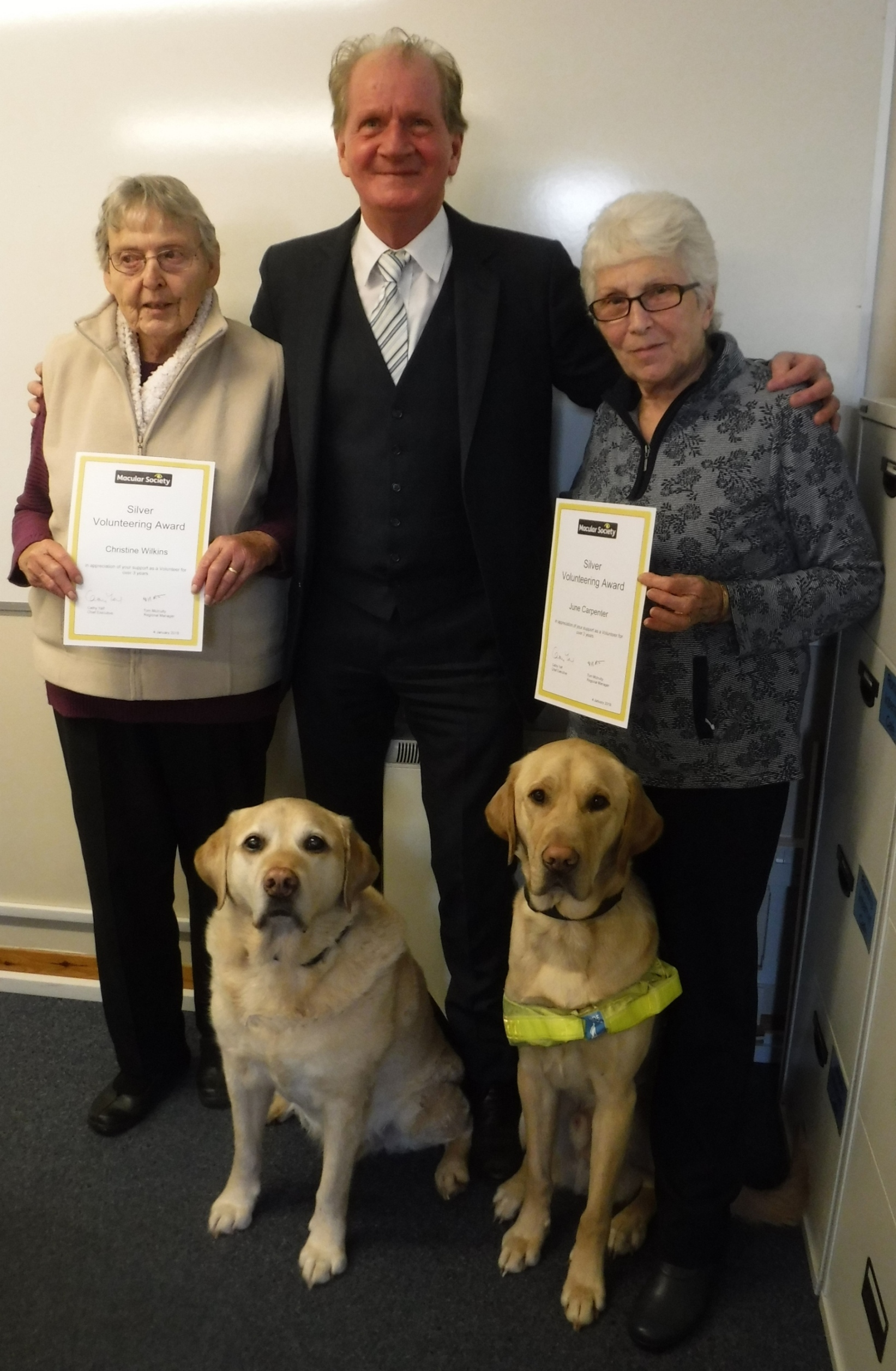 Christine Wilkins (left) and June Carpenter (right) receive their awards from Macular Society regional manager Tom McInulty and guide dogs Brunel and Toby.