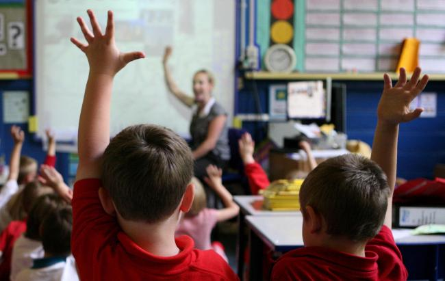 File photo dated 06/07/11 of children at school raising their hands to answer a question, as Labour warned that more than half a million primary school children are now being taught in
